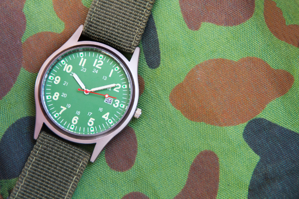 Military Watch on camo cloth. Military personnel wear watches inside their wrists for several reasons.