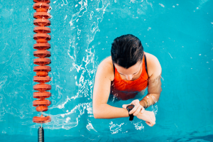 Type 2 (50m) and Type 3 (100m) Watches are ok for swimming. Woman in orange bathing suite in blue water of swimming pool checking watch