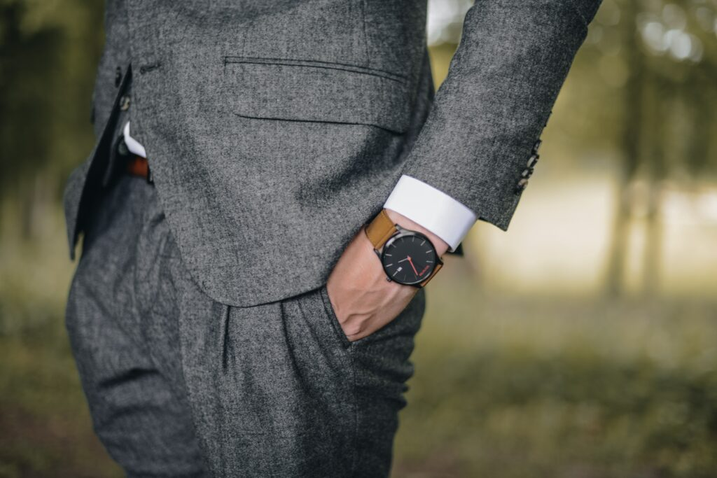 man in gray suit with watch on left hand,  Which wrist to Wear Watch?  Place it on your non dominant hand.
