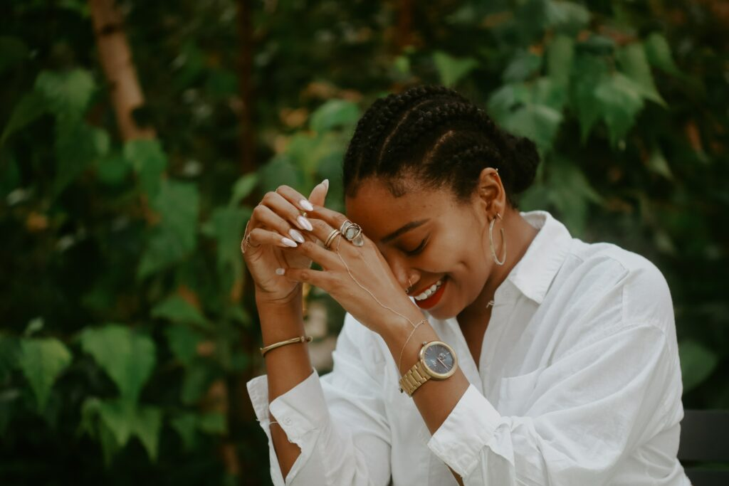 In this article, we answer the question - Which Wrist to Wear A Watch - Female .  In the photo, and African American woman in a white blouse wears a gold watch on her left hand.