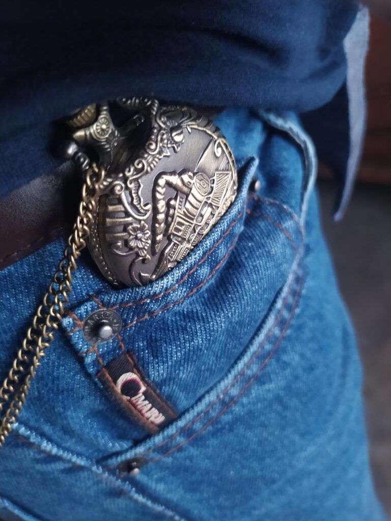 ornate pocket watch in the pocket of blue jeans.  Chain is visible
