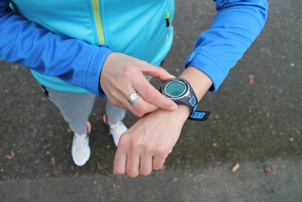 person wearing athletic clothes looking at watch. You can wear a watch almost all of the time.