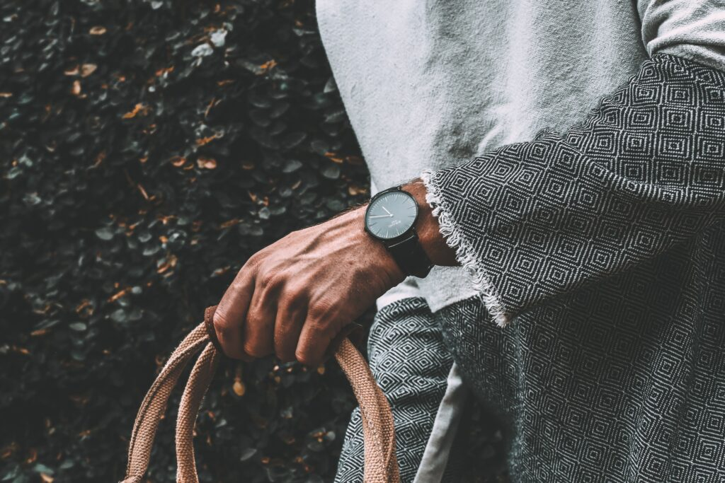 person carrying bag while wearing a watch on the left hand. Where to Wear a Watch?  Comfort and Etiquette and Fashion all play a role.