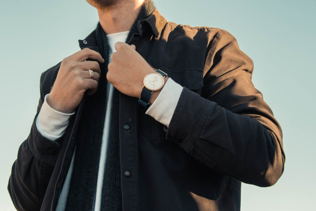 Man in Leather Jacket wearing a watch with a leather band.  Men Wear Watch in Which Hand?  One answer possible answer to the question is whichever wrist it feels most comfortable.