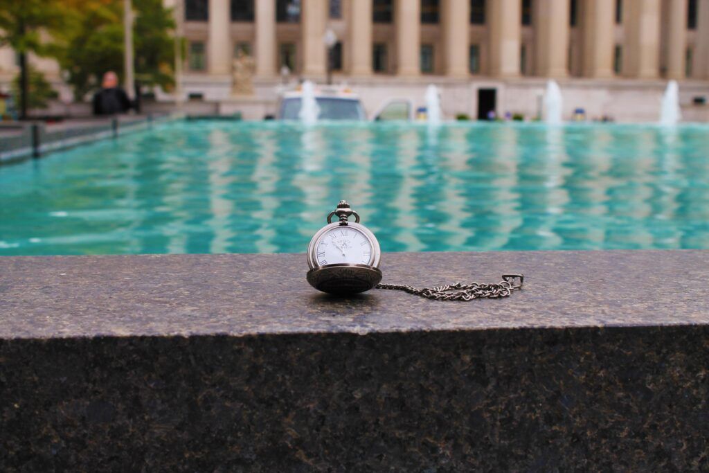 pocket watch near the side of a reflecting pool