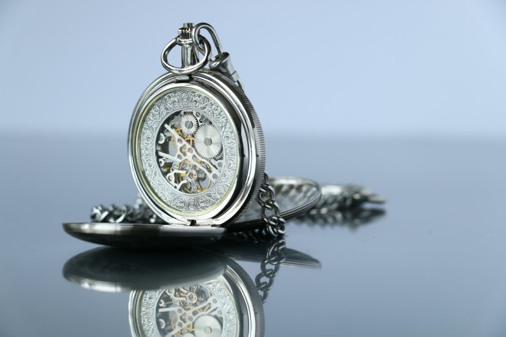 Silver Pocket watch attached to a chain.  When was the pocket watch invented?  It goes back to 1510