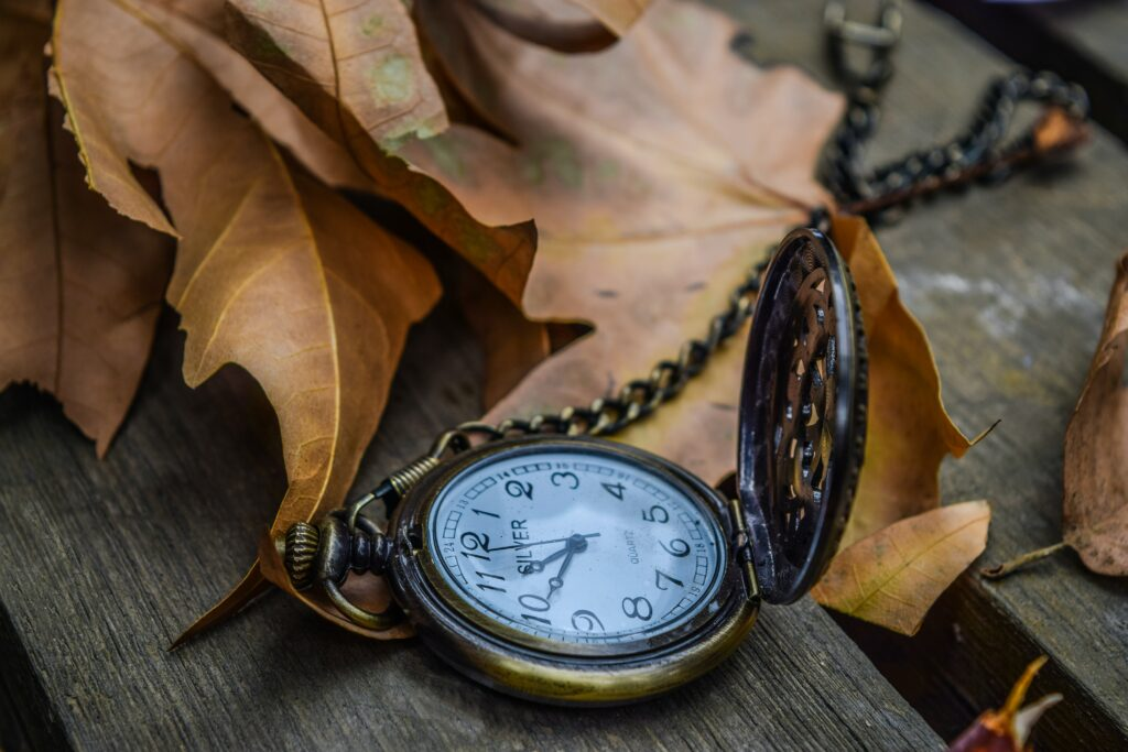 rustic pocket watch on a wooden table in autumn leaves