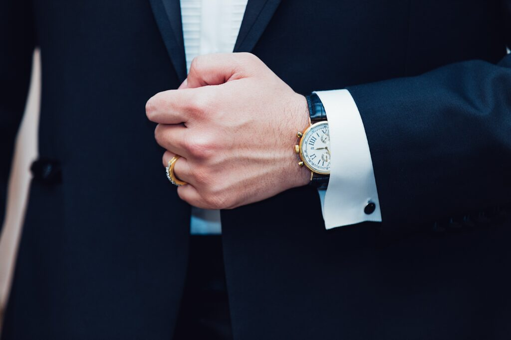 man wearing suit and wearing watch on left hand. Men Wear Watch In Which Hand?  The non Dominant hand.