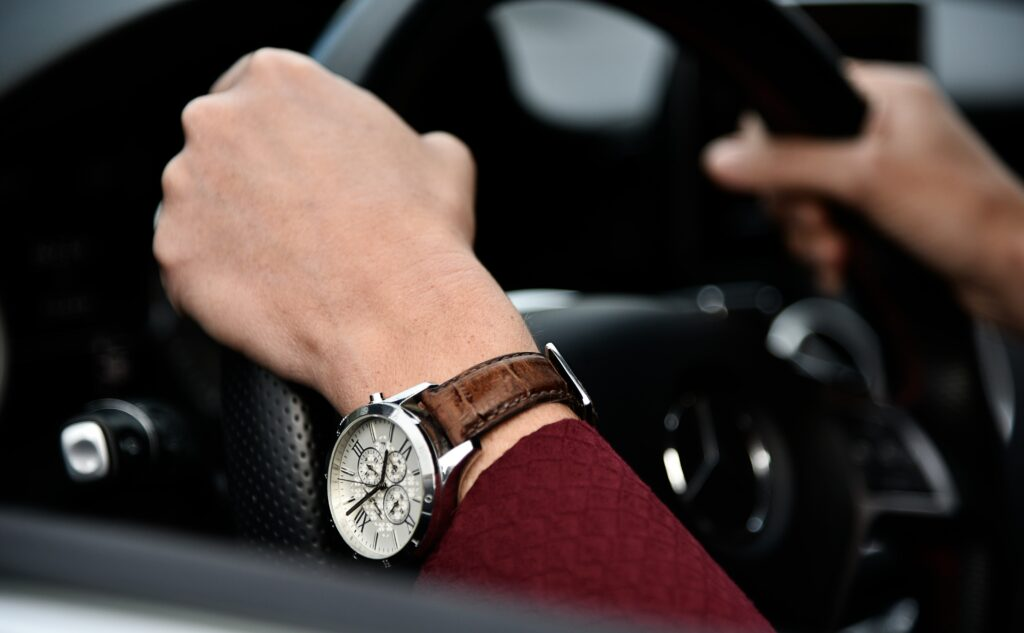 Hands on a steering wheel with a watch on the left hand that is not centered on wrist.  How to properly wear a watch?  It shouldn't move by more than one inch.