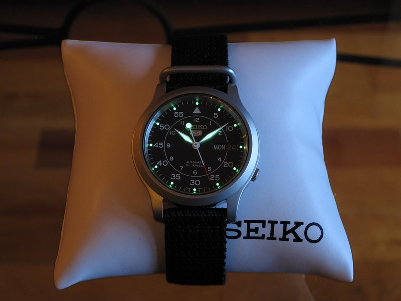 Seiko SNK809 on Display. Note Luminous Hands. On a glass table against hardwood floor. Source: Matthew Kendall on Flickr https://www.flickr.com/photos/mdkendall/8305821190/