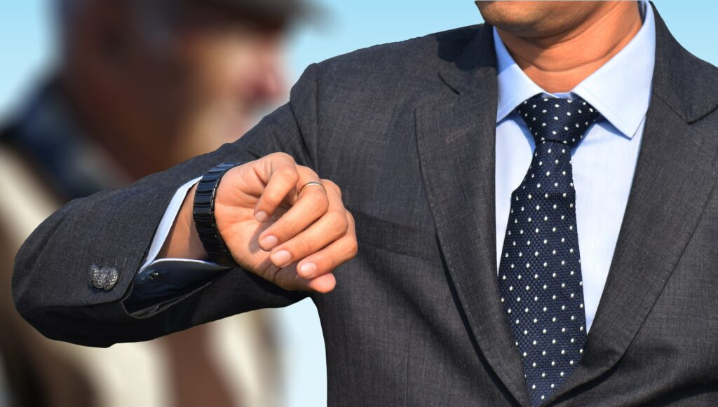 man wearing a gray suit looking at his watch on his right hand.  What does wearing a watch on the right hand mean?  You may be creative.  You may be showing off the watch.  You may be left handed.