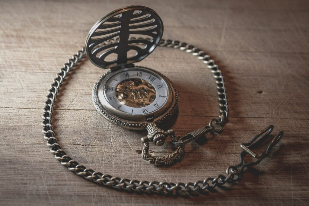 open pocket watch on a table with chain attached