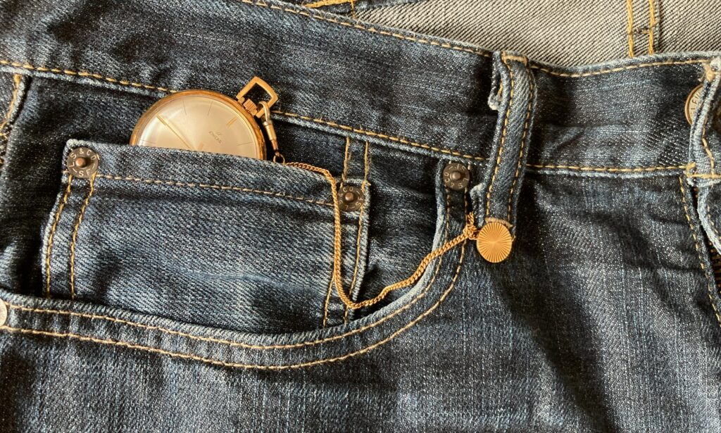 gold pocket watch attached to blue jeans by chain