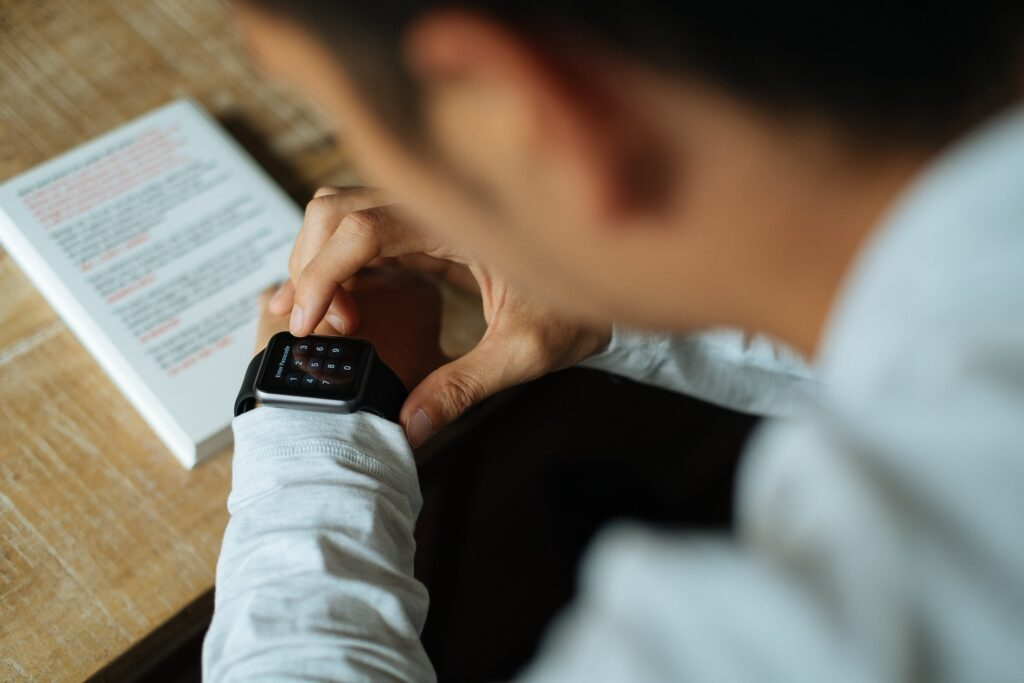man wearing white long sleeved shirt looking at watch on left arm. When considering whether to position the watch above or below wrist bone with a long sleeved shirt, know that your watch should not be visible when you stand with your arms at the side.