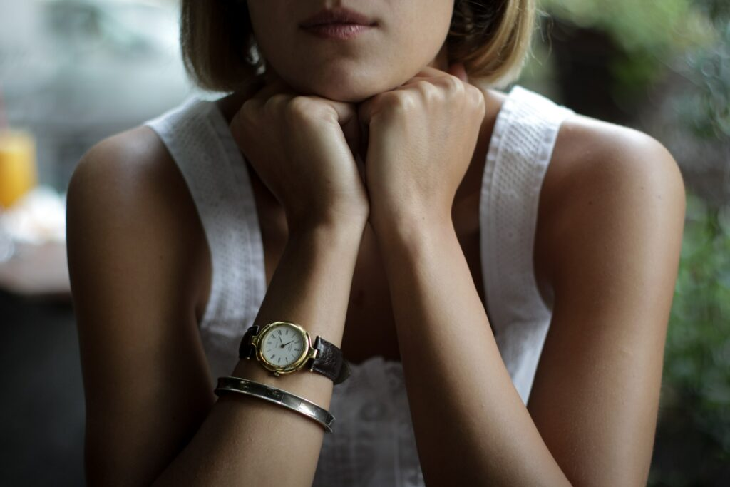 What side do women wear watches? Traditionally, women wore watches on their right hand.  This shows a woman in a white shirt with her arms propping up her neck.  She has a bracelet and a watch on her right hand.