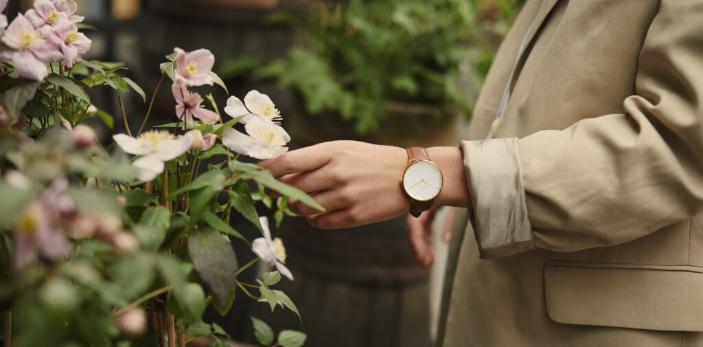 Which hand do you wear a watch on?  Woman wearing a watch on her left hand standing near flowers