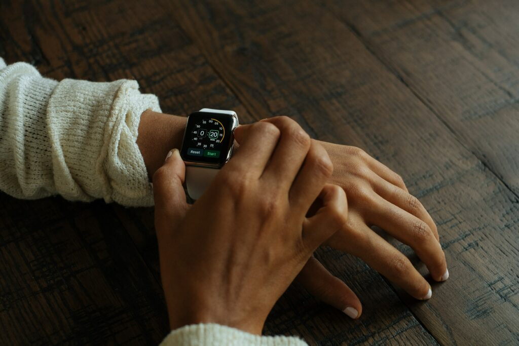 What write to wear Apple watch?  Here is a person wearing an Apple Watch on their left hand and adjusting it with their right hand.