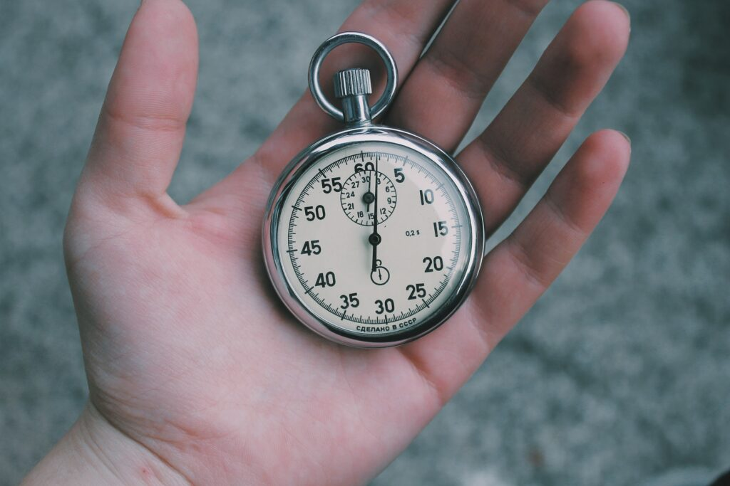 Silver stopwatch in a hand.  How to read a stopwatch. This is a traditional stopwatch, also known as an analog stopwatch.  It has one button that causes it to stop and start.  You read the seconds on the outer scale and the minutes in the small inner scale.