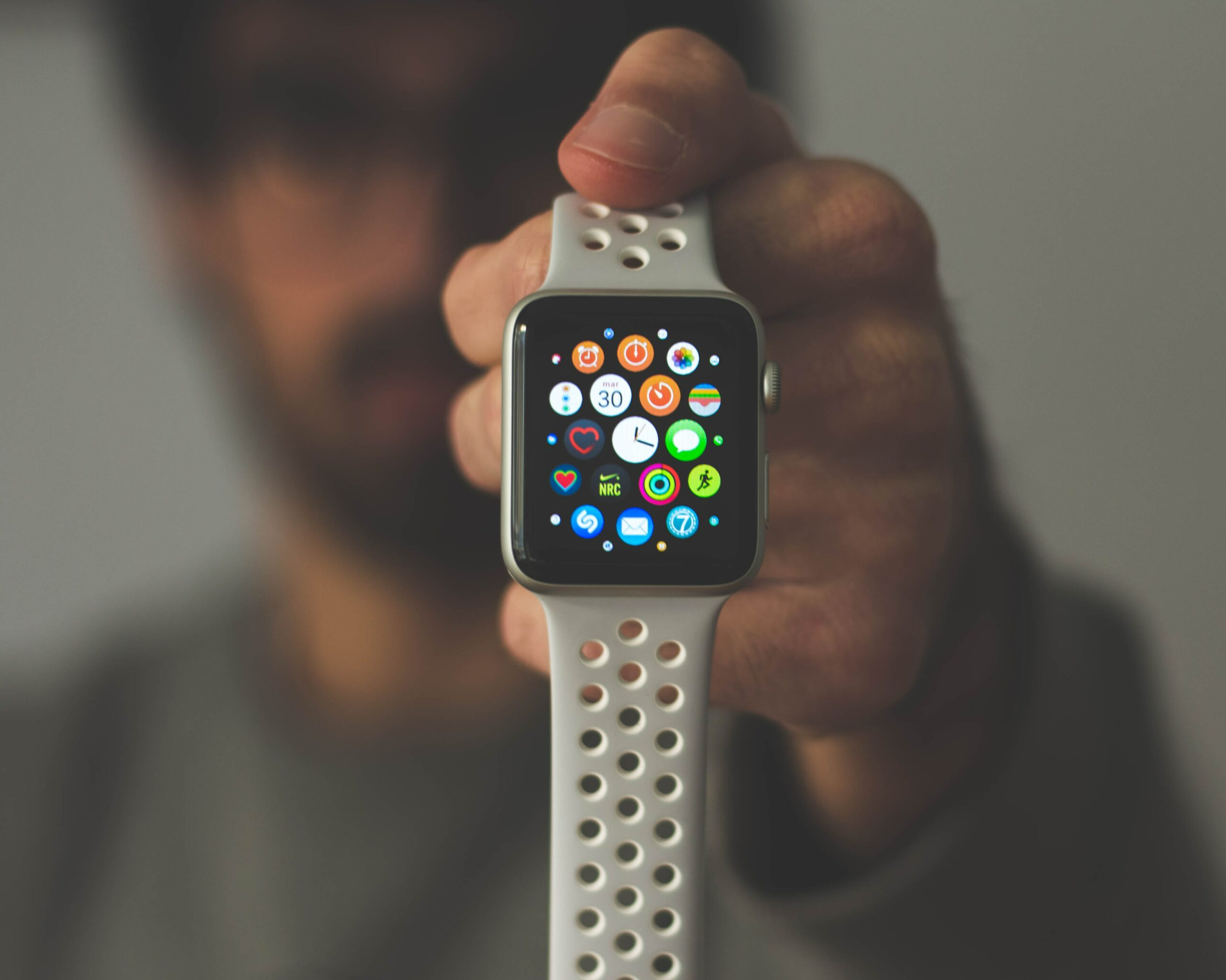 man blurred out behind an Apple Watch