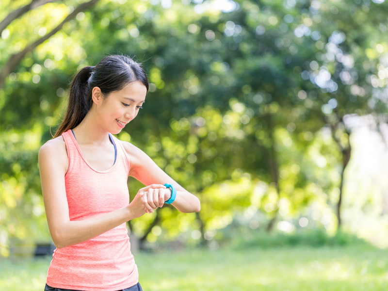 Female Runner checks her Apple Watch.  Apple Watch should be tight enough to accurately read you heart rate