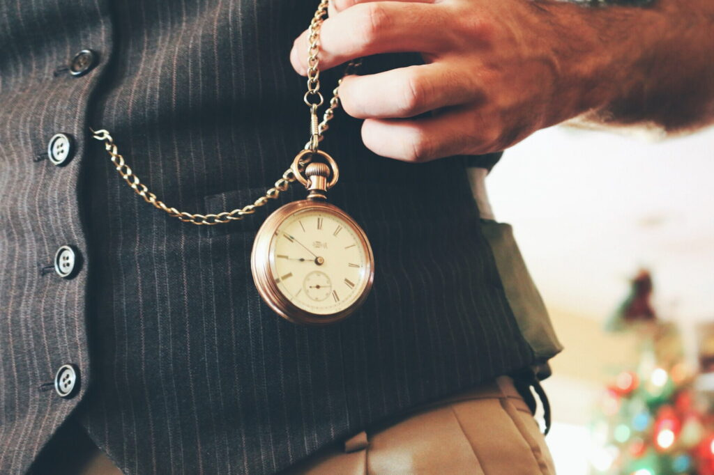 Right handed people typically handled pocket watches with their left hand.  This has carried over to wrist watches - they are worn on the non dominant wrist.  This photo shows a man in a vest handling a pocket watch with his left hand.