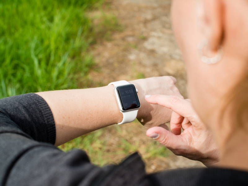 A woman checks her Apple Watch while she is outside.  The watch has a white band.