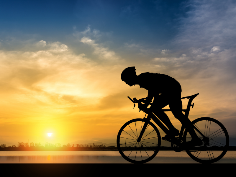 Silhouette of biker against sunset. Explore the best cycling watch and best watch for biking